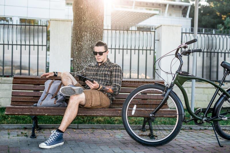 Młodego Człowieka cyklista Odpoczywa Na ławce I Używa pastylki Cyfrowego przyrządów technologii Komunikacyjnego Podłączeniowego p zdjęcie royalty free