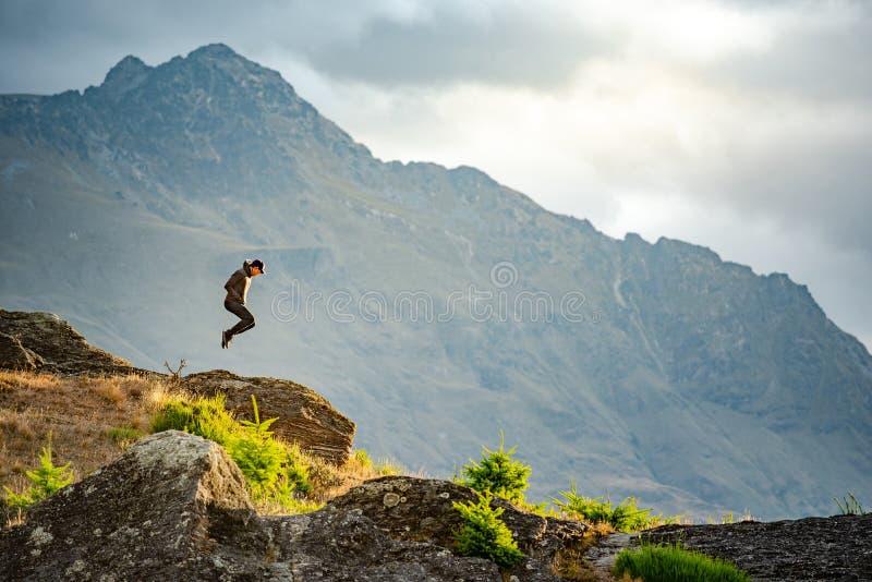 Młodego człowieka doskakiwanie na Queenstown wzgórzu, Nowa Zelandia zdjęcia royalty free