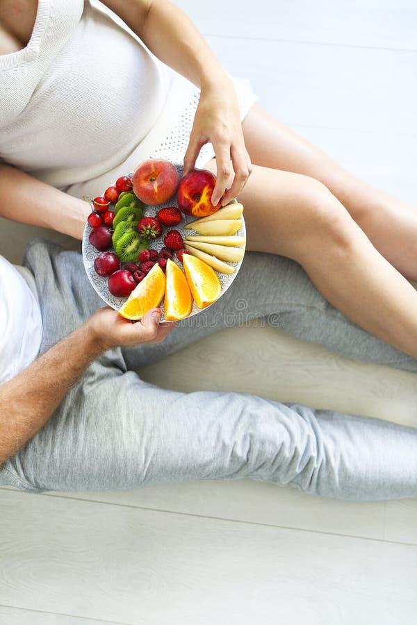 Młodego człowieka i kobieta w ciąży obsiadanie z owoc talerzem obrazy royalty free