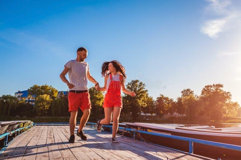 Młodego człowieka i kobiety bieg wzdłuż lato rzecznego doku Para ma zabawę przy zmierzchem Facetów relaksować obrazy stock