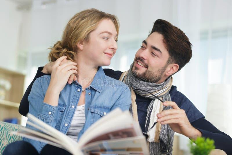 Młodego człowieka i kobiety czytelnicze książki na kanapie obraz stock