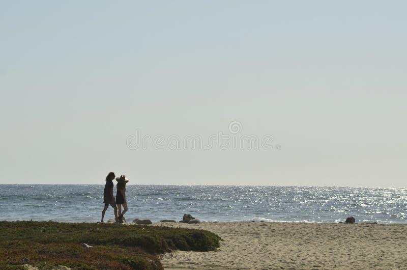 Młodego człowieka i kobiety pary sylwetki chodzi Pacyfik plażowy Baj, Meksyk fotografia stock