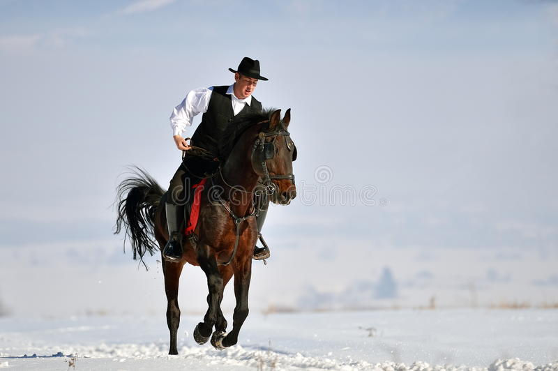 Młodego człowieka jeździecki koń plenerowy w zimie obrazy stock