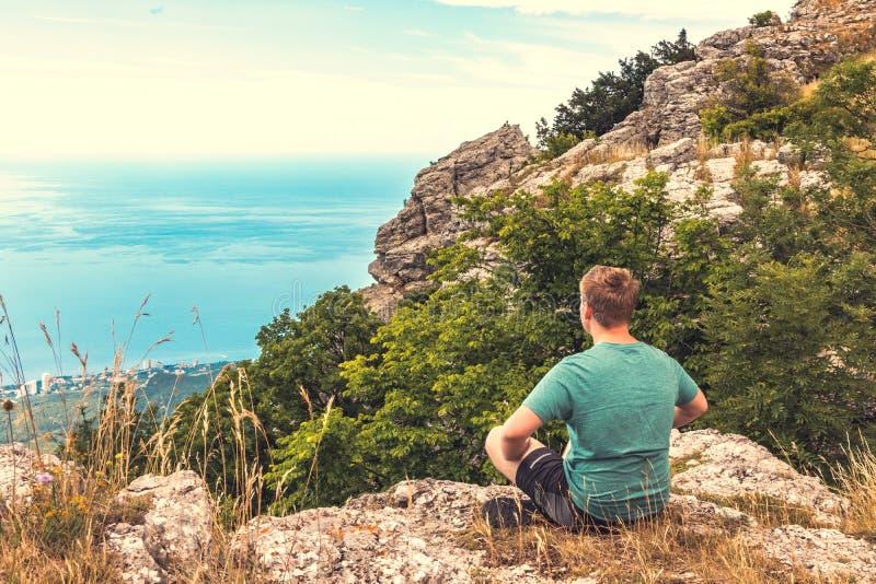 Młodego człowieka joga pozy ćwiczy obsiadanie na skalistym szczycie Mężczyzna robi medytacji i cieszyć się widokowi zdjęcia stock