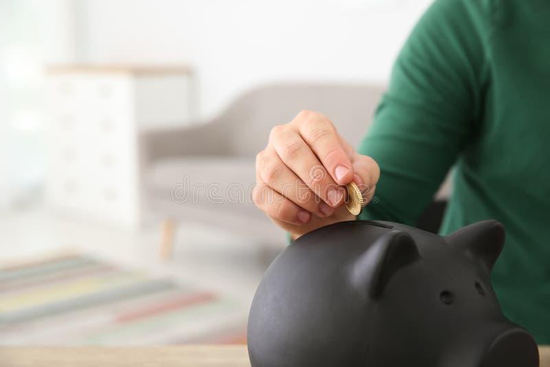 Młodego człowieka kładzenia moneta w prosiątko banka zdjęcia royalty free