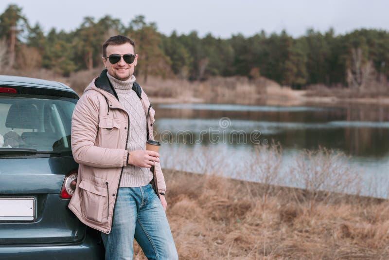 Młodego człowieka kierowca zatrzymujący i odpoczywa z filiżanka kawy blisko samochodu podczas podróży przerwy obraz royalty free