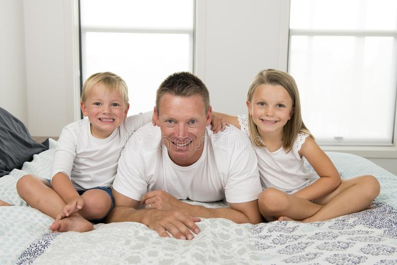Młodego człowieka lying on the beach na łóżku wraz z jej małym cukierki 3 i 7 lat córki i syna bawić się szczęśliwy w rodzinnych  zdjęcie stock
