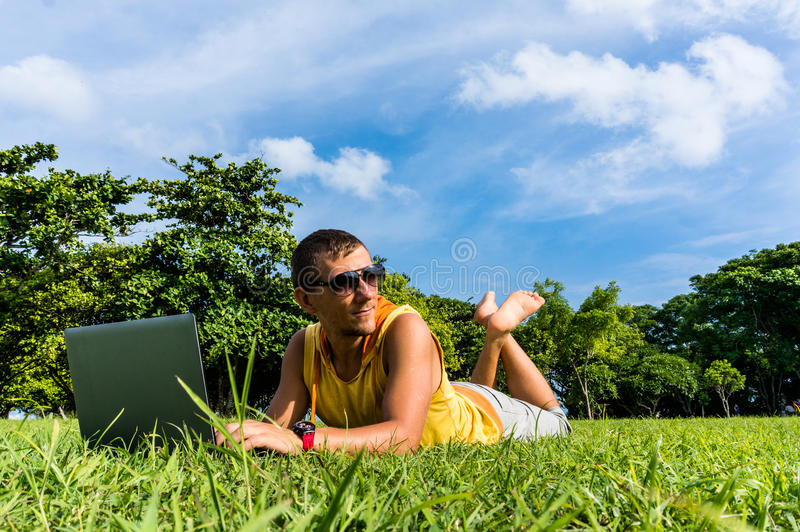 Młodego człowieka lying on the beach na trawie i działanie z laptopem zdjęcie royalty free