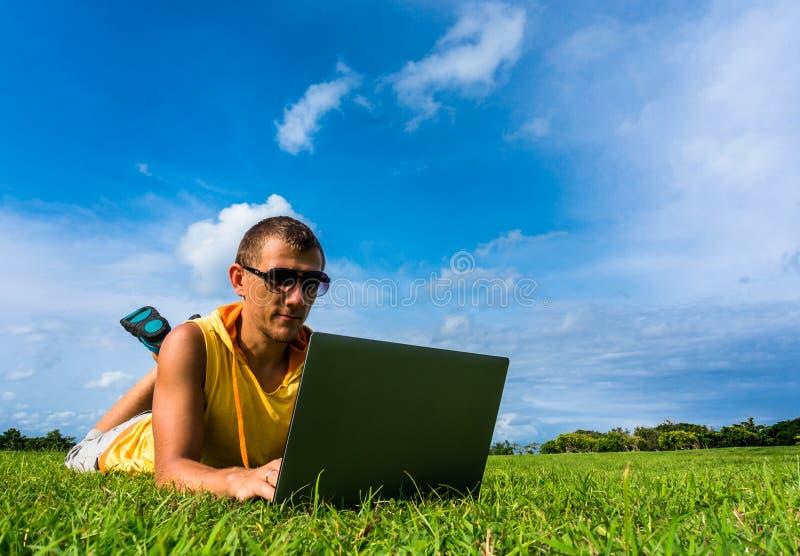 Młodego człowieka lying on the beach na trawie i działanie z laptopem obraz royalty free