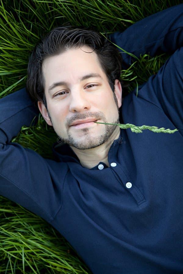 Młodego człowieka lying on the beach na zielonych gras zdjęcie royalty free