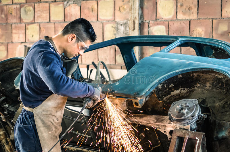 Młodego człowieka machinalny pracownik naprawia starego rocznika samochód fotografia royalty free