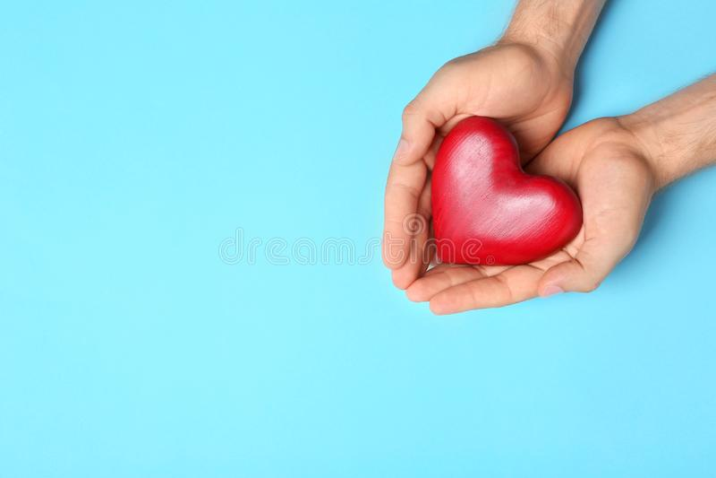 Młodego człowieka mienia czerwony serce na bławym tle, przestrzeń dla teksta Darowizny poj?cie zdjęcie stock