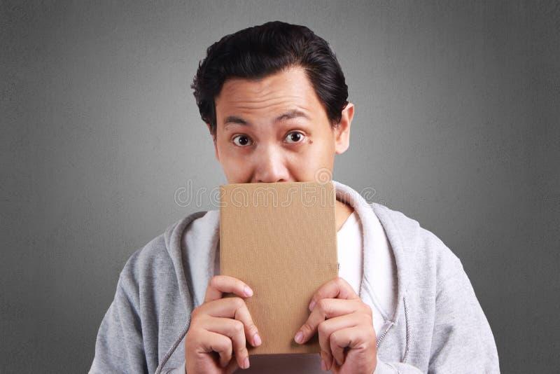 Młodego Człowieka mienia książka, usta Zakrywający książką obraz stock