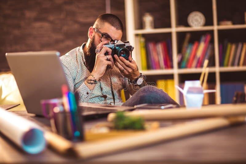 Młodego człowieka mienia obsiadanie stołem z komputerem i kamera zdjęcia stock