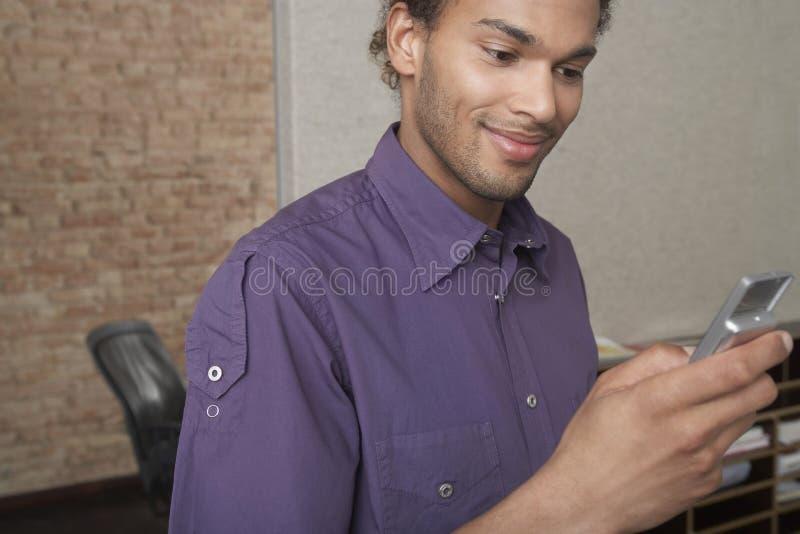 Młodego człowieka mienia telefon komórkowy W biurze obraz stock