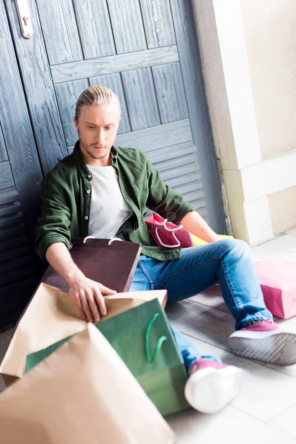 Młodego człowieka mienia torba na zakupy podczas gdy odpoczywający i siedzący na podłoga fotografia royalty free