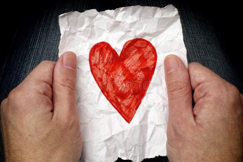 Młodego człowieka mienia zmięty kawałek papieru z czerwonym sercem fotografia royalty free