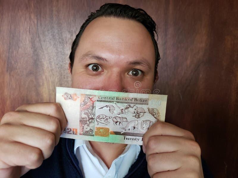 młodego człowieka mienie i seans belizean banknot dwadzieścia dolarów obrazy royalty free