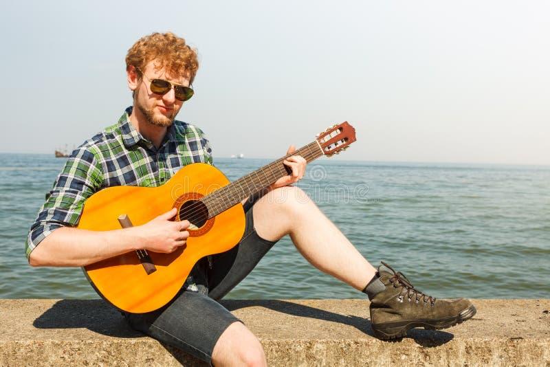Młodego człowieka modniś bawić się gitarę dennym oceanem fotografia royalty free
