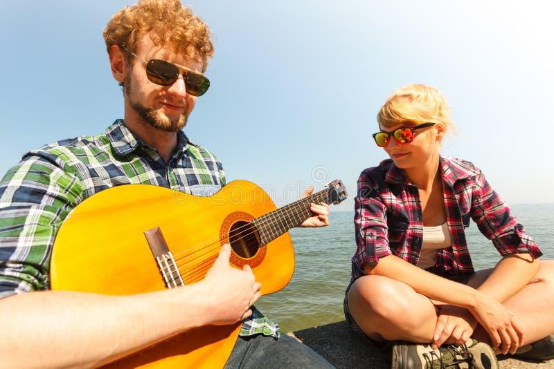 Młodego człowieka modniś bawić się gitarę dla kobiety obrazy royalty free