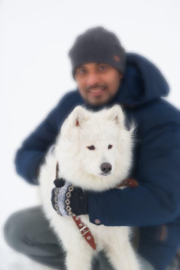 Młodego człowieka obejmowania stały biały puszysty pies w zimie Seective ostrość w psie obrazy royalty free