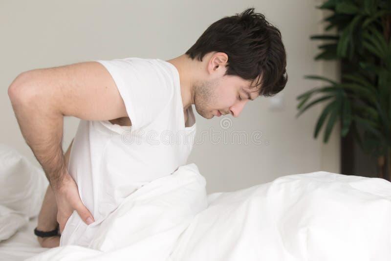 Młodego człowieka obsiadanie na łóżku dotyka boleć z powrotem w domu zdjęcie royalty free