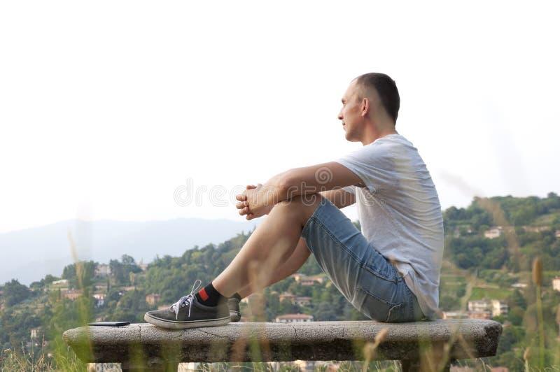 Młodego człowieka obsiadanie na ławce przy miasto widokami obrazy stock