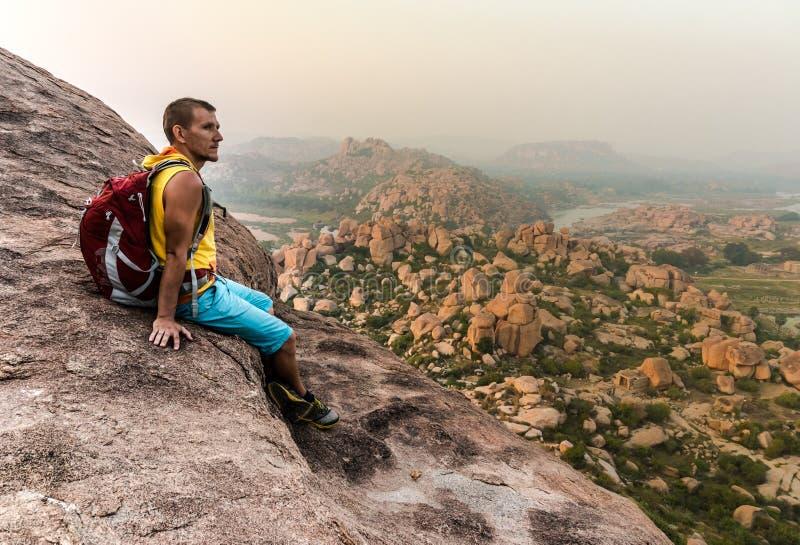 Młodego człowieka obsiadanie na górze i cieszyć się widok po trekking zdjęcia stock