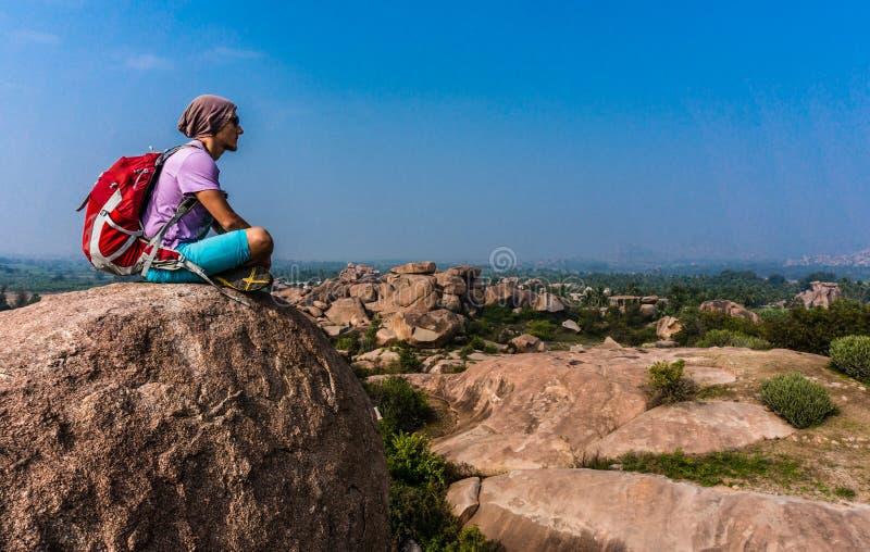 Młodego człowieka obsiadanie na górze i cieszyć się widok po trekking zdjęcie royalty free