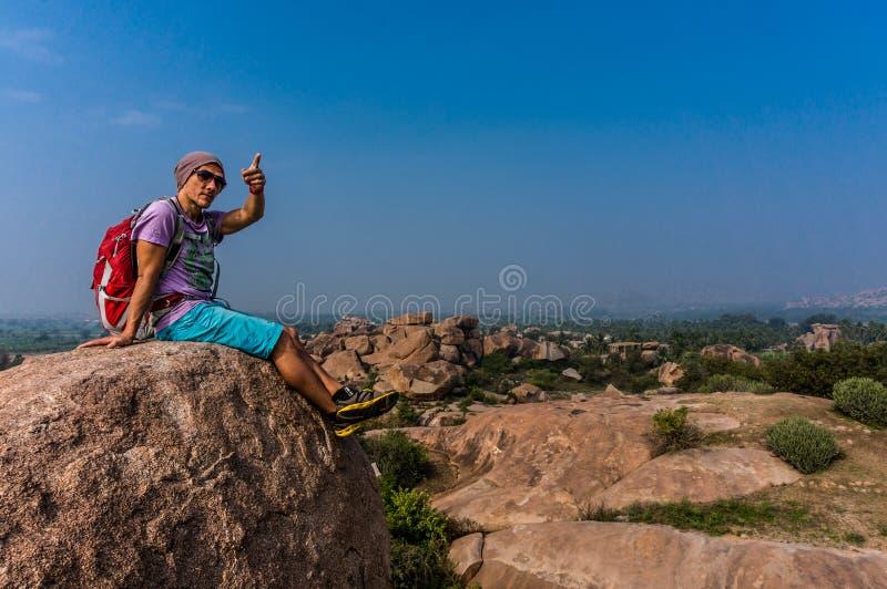 Młodego człowieka obsiadanie na halnym, enjoing widok po trekking obraz stock