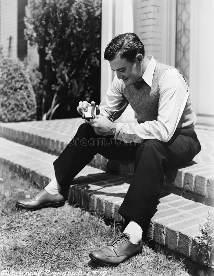 Młodego człowieka obsiadanie na mieniu i kroku papierosowa zapalniczka z drymbą (Wszystkie persons przedstawiający no są długiego fotografia royalty free