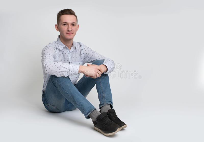 Młodego człowieka obsiadanie na podłoga odizolowywającej zdjęcia royalty free