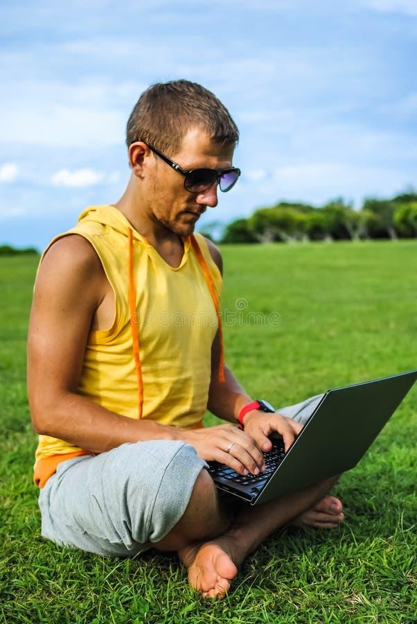 Młodego człowieka obsiadanie na trawie i działanie z laptopem zdjęcia stock