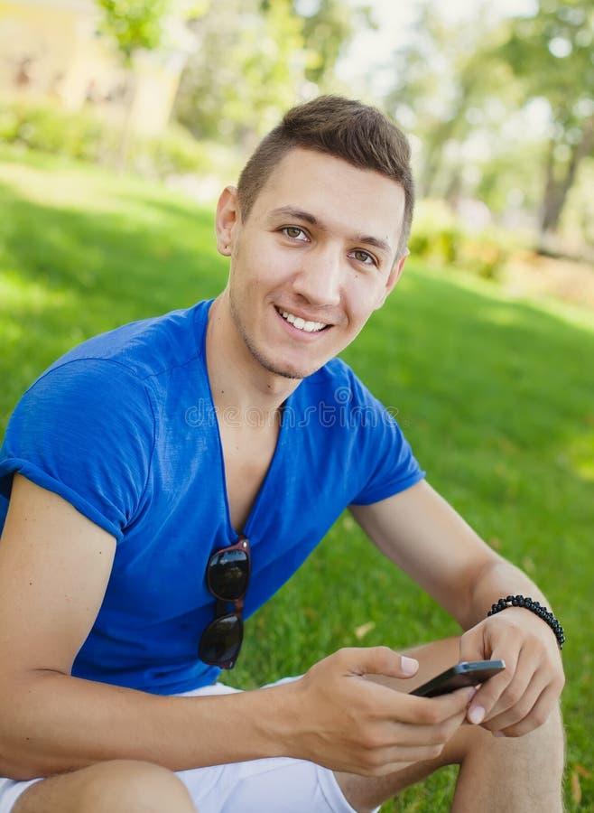 Download Młodego Człowieka Obsiadanie Na Trawie I Używać Mądrze Telefon Zdjęcie Stock - Obraz złożonej z optymistycznie, szczęście: 57653614