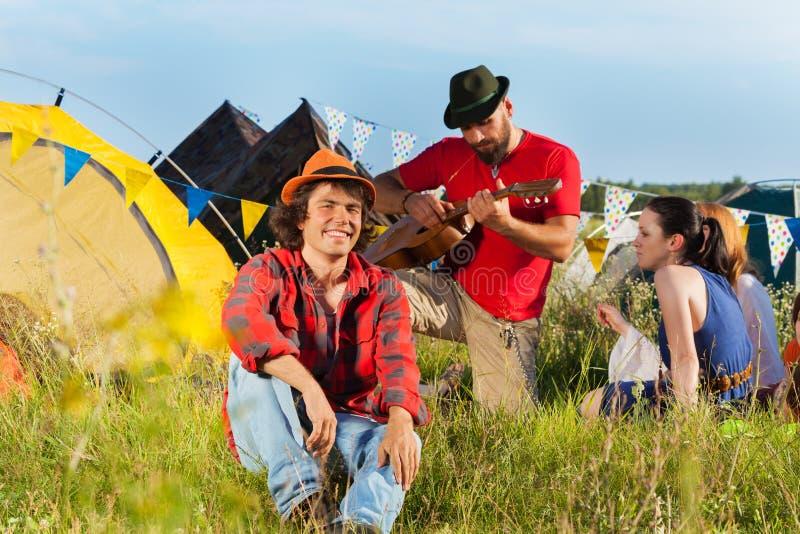 Młodego człowieka obsiadanie na trawie przy fest z przyjaciółmi obraz stock