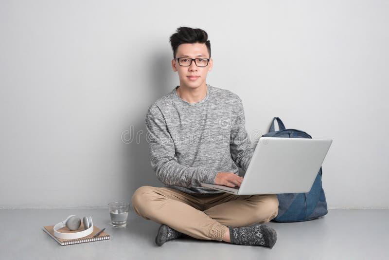 Młodego człowieka obsiadanie na używać laptopie i podłoga zdjęcia royalty free