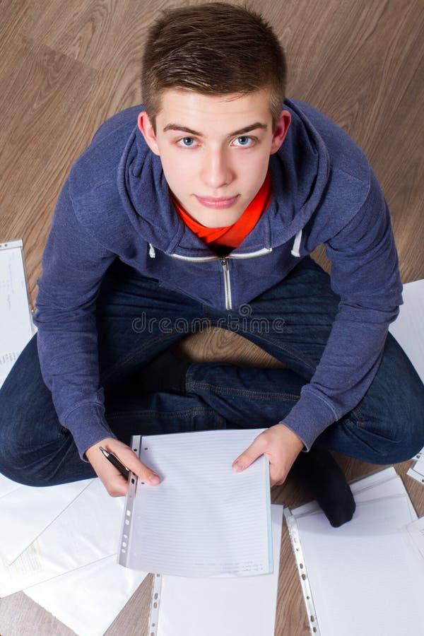 Młodego człowieka obsiadanie na uczenie i podłoga obrazy stock