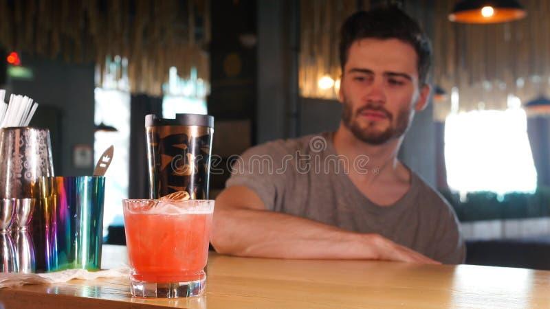 Młodego człowieka obsiadanie prętowym stojakiem i patrzeć szkło z koktajlem zdjęcie stock