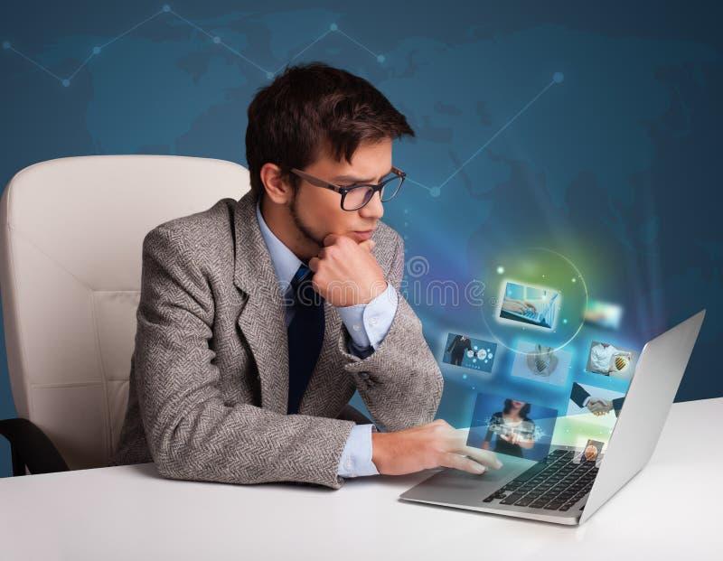 Młodego człowieka obsiadanie przy biurkiem i dopatrywaniem jego galeria zdjęć na lapt obrazy royalty free