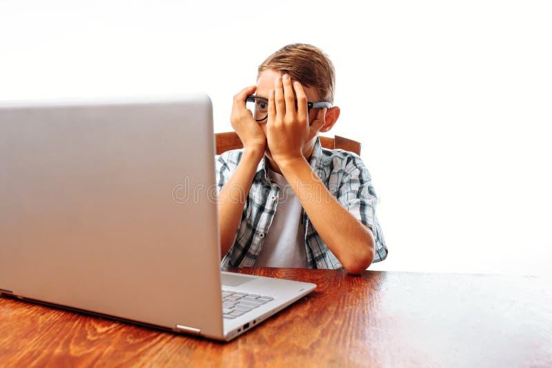 Młodego człowieka obsiadanie przy stołem z laptopem, szokującym, nastoletni zdziwiony spojrzenie przy laptopem na białym tle w, c zdjęcia royalty free