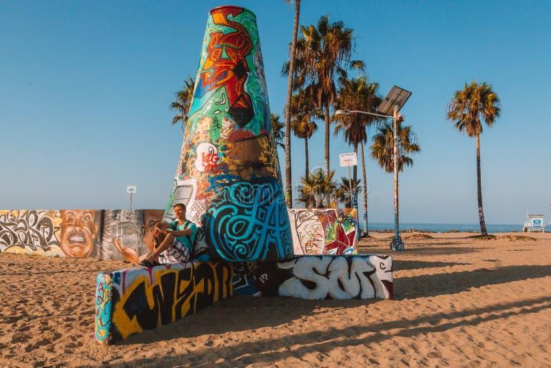 Młodego człowieka obsiadanie przy Wenecja plażą obrazy stock