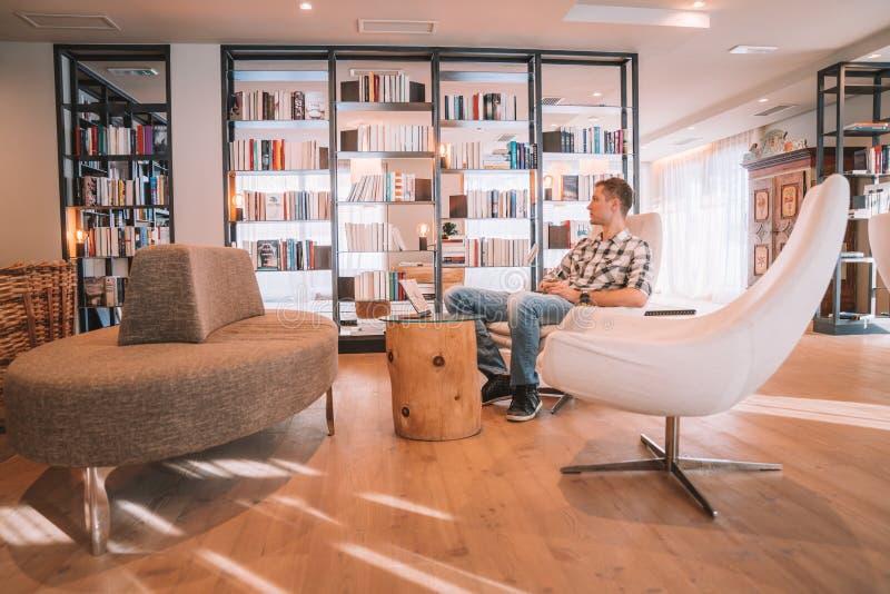 Młodego człowieka obsiadanie w krześle w wygodni biblioteczni izbowi pobliscy ogromni okno obrazy royalty free