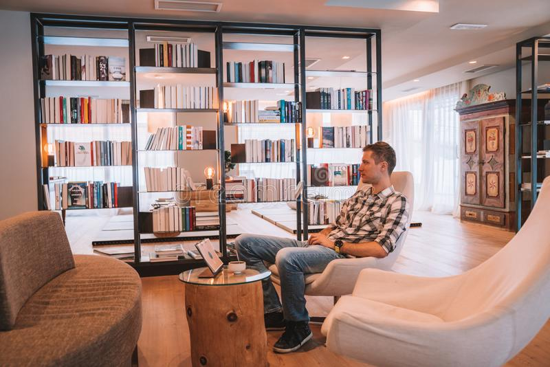 Młodego człowieka obsiadanie w krześle w wygodni biblioteczni izbowi pobliscy ogromni okno fotografia stock