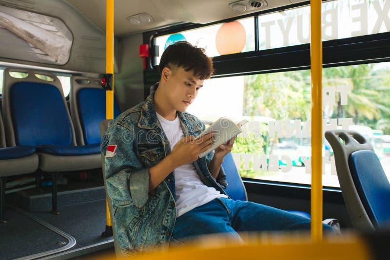 Młodego człowieka obsiadanie w miasta czytaniu i autobusie książka fotografia stock
