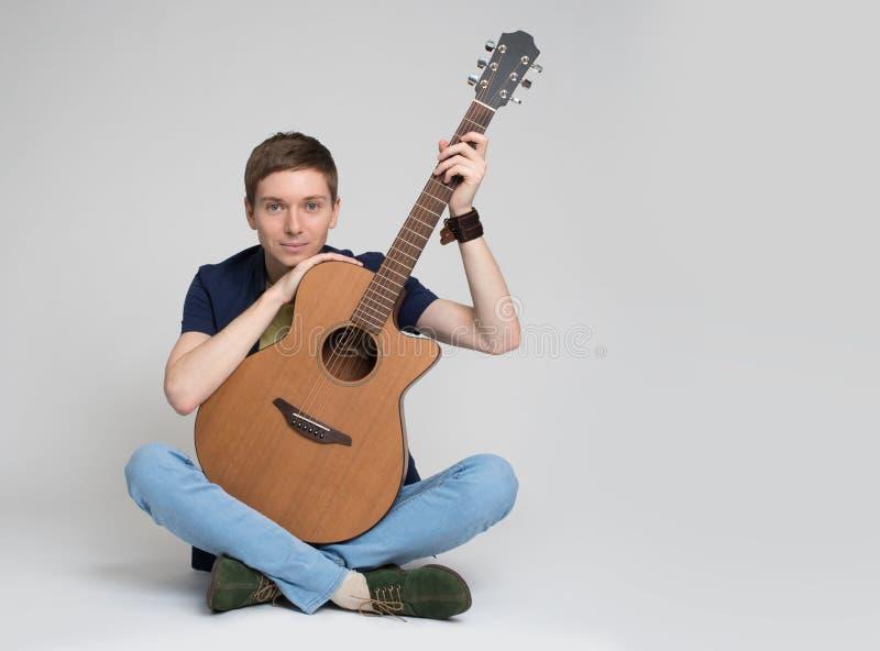 Młodego człowieka obsiadanie z gitarą zdjęcie royalty free