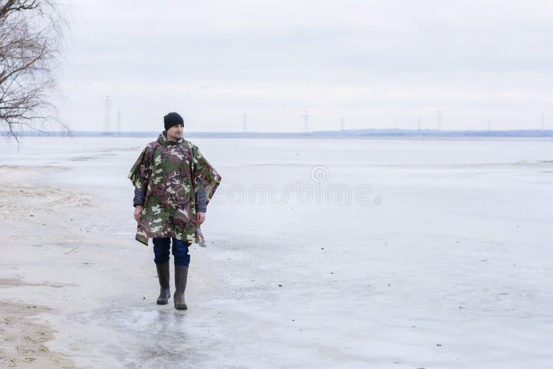 Młodego człowieka odprowadzenie na plaży ogląda zamarzniętą wodę w militarnym podeszczowym żakiecie fotografia stock