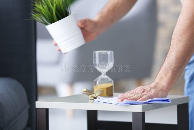 Młodego człowieka okurzania stół podczas gdy czyści mieszkanie, obraz royalty free
