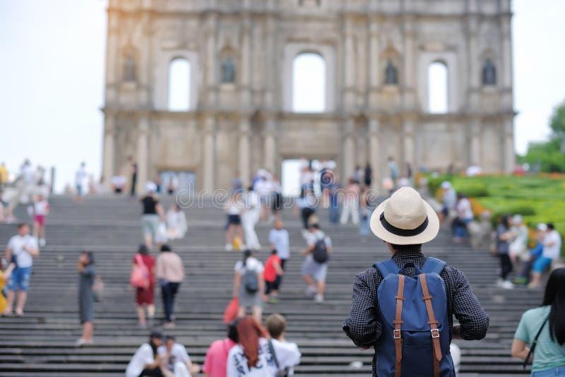 Młodego człowieka podróżny backpacker z kapeluszem, Azjatycki modnisia podróżnik patrzeje ruiny St Paul, Historyczny Centre Macau zdjęcia royalty free