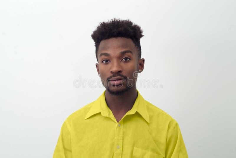 Młodego człowieka portret w żółtej koszula na białym tle obrazy stock