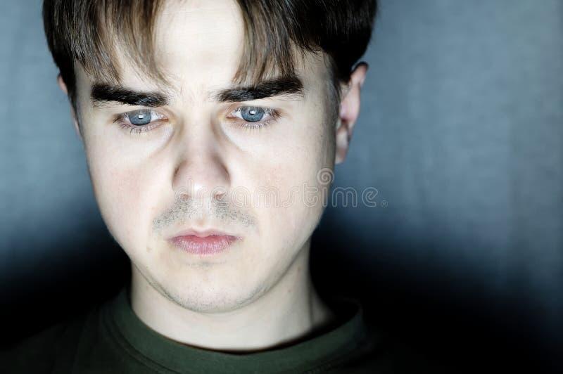 Młodego człowieka portret w ciemnym pokoju przy ciemnym tłem, młody człowiek pracuje przy komputerem, poważny programisty cyfrowa zdjęcia stock
